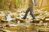 pic of legs feet  - Hiker man with backpack crossing a river on stones in autumn forest view of legs - JPG