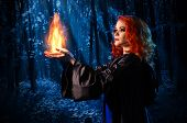 picture of witch  - Young witch in the night forest holds fire - JPG