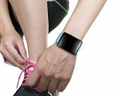 Woman Hand Tying Shoelaces Wearing Smartwatch With Bright Green Watchband
