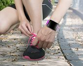 Human Hand Tying Shoelaces Wearing Smartwatch With Bright Pink Watchband
