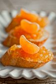 pieces of baguette with orange marmalade closeup on white plate