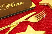 Christmas golden cutlery and restaurant menu on festive background