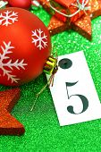 Number five on tag and Christmas ornamets on green background