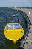 Yellow Motor Boat Near Sea Dock And Lighthouse
