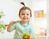 kid girl eating healthy vegetables food
