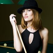 image of hustler  - Portrait of the beautiful woman in black dress and hat with cue - JPG
