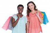 Female friends holding shopping bags on white background