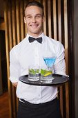 Cheerful young waiter holding tray with cocktails in a bar