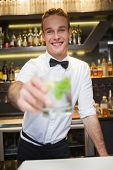 Happy bartender offering cocktail to camera in a bar