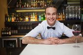 Smiling bartender having glass of red wine in a bar