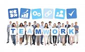 Multi-ethnic group of business and casual people holding cardboards forming teamwork and related symbols above.