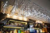 Many wine glasses hanging above the bar in a nightclub