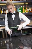 Cute woman in suit pouring champagne into flute in a bar