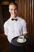Waiter holding tray with coffee cup in a bar