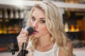 Young blonde woman singing while looking at camera at the nightclub