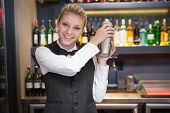 Pretty blonde waitress shaking cocktail in a bar