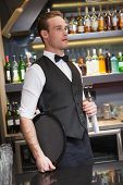 Serious waiter holding tray and towel in a bar