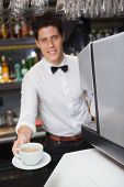 Barista offering cup of coffee smiling at camera in a cafe