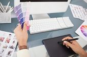 Designer working at desk using digitizer and colour sample in his office