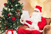 christmas, holidays and people concept - man in costume of santa claus with letter and christmas tree over beige lights background