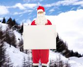 christmas, holidays, advertisement and people concept - man in costume of santa claus with white blank billboard over snowy mountains background