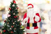 christmas, holidays, gesture and people concept - man in costume of santa claus with bag and christmas tree showing thumbs up over lights background