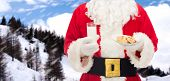 christmas, holidays, food, drink and people concept - close up of santa claus with glass of milk and cookies over snowy mountains