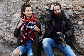 Attractive bearded hipster and young charming girl sitting on rock