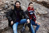 Beautiful couple of hipsters smiling sitting on mountain rock