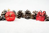 Two Red Christmas Baubles With Pine Cones On Snow In Line On Whi