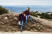 Couple of hikers resting sitting on mountain hill with beautiful view on background, stylish couple