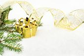 Gold Christmas Gifts With Gold Ribbon And Needles Fir On Snow