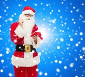 christmas, holidays and people concept - man in costume of santa claus with notepad and pen over blue snowy background