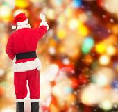 christmas, holidays and people concept - man in costume of santa claus writing something from back over red lights background