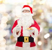christmas, holidays, food, drink and people concept - man in costume of santa claus with glass of milk and cookies over lights background
