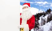 christmas, holidays, advertisement and people concept - man in costume of santa claus with white blank billboard over snowy mountains