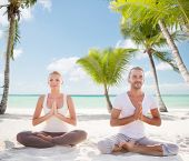 sport, yoga, people, travel and lifestyle concept - smiling couple meditating sitting on tropical beach