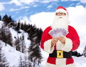 christmas, holidays, winning, currency and people concept - man in costume of santa claus with euro money over snowy mountains