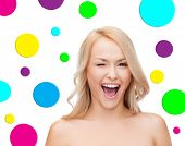 people and beauty concept - beautiful smiling young woman winking one eye over colorful polka dot pattern background