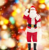 christmas, holidays, gesture and people concept - man in costume of santa claus with bag pointing finger up over red lights background