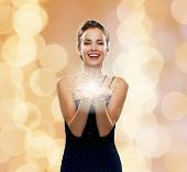 holidays and people concept - laughing woman in evening dress holding something over beige lights background