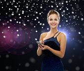 technology, christmas, holidays and people concept - smiling woman in evening dress holding smartphone over night lights and snow background