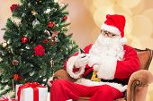 holidays, technology and people concept - man in costume of santa claus with smartphone, presents and christmas tree over beige lights background