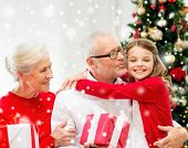 family, holidays, generation, christmas and people concept - smiling grandparents and granddaughter with gift boxes sitting on couch at home
