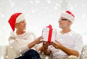 family, holidays, christmas, age and people concept - happy senior couple in santa helper hats with gift box at home