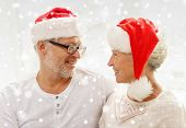 family, holidays, christmas, age and people concept - happy senior couple in santa helper hats looking to each other at home