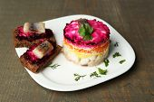 Russian herring salad on plate and sandwich with salted herring, on wooden table background