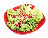 Fresh salad with greens, garnet and spices on plate isolated on white
