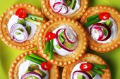 Tartlets with greens and vegetables with sauce on plate close-up
