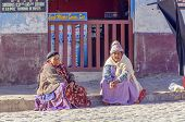 COPACABANA, BOLIVIA, MAY 6, 2014:  Local women in traditional costumes chat outdoor